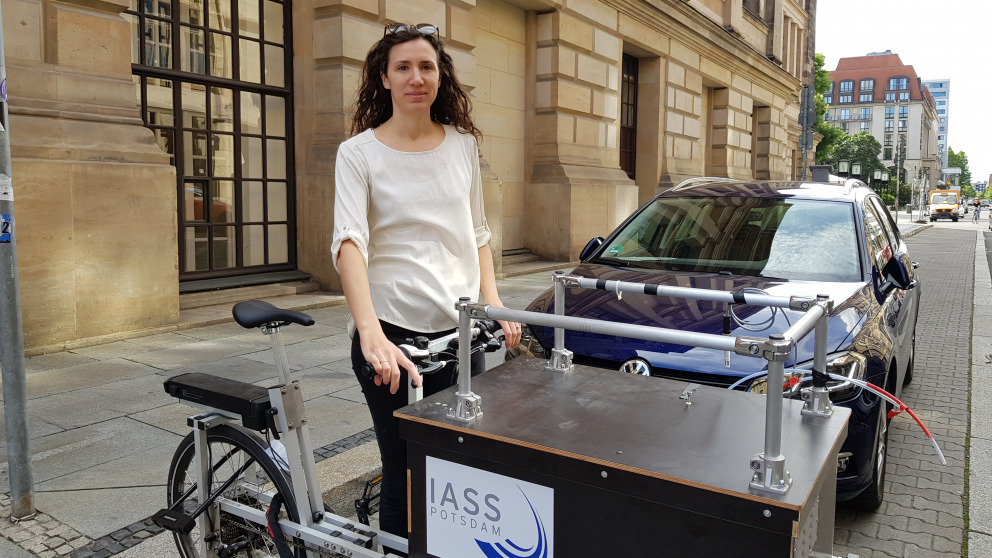 IASS researcher Erika von Schneidemesser with a bicycle for mobile air quality monitoring on Charlottenstrasse in Berlin. The cargo bike can be parked at different locations to measure air quality.