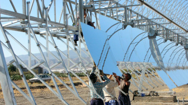 Workers install a reflective parabolic trough at a solar thermal power plant in Spain.