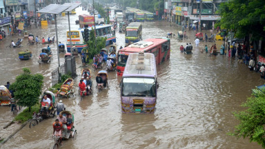 Dhaka, Bangladesh: People and vehicles wade through a water-logged road after heavy rains in Dhaka.